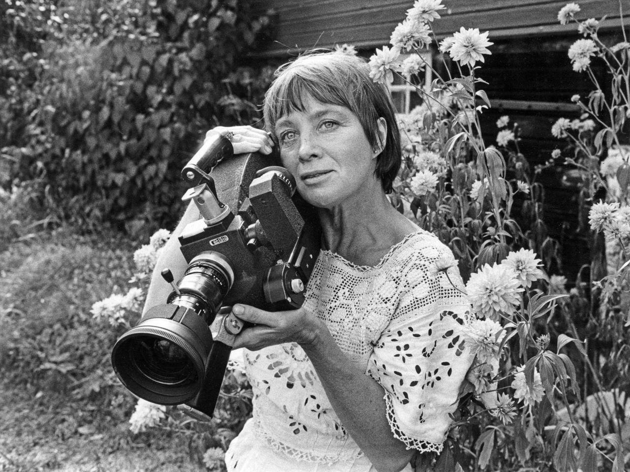 Mai Zetterling in later years posing with a camera in her garden