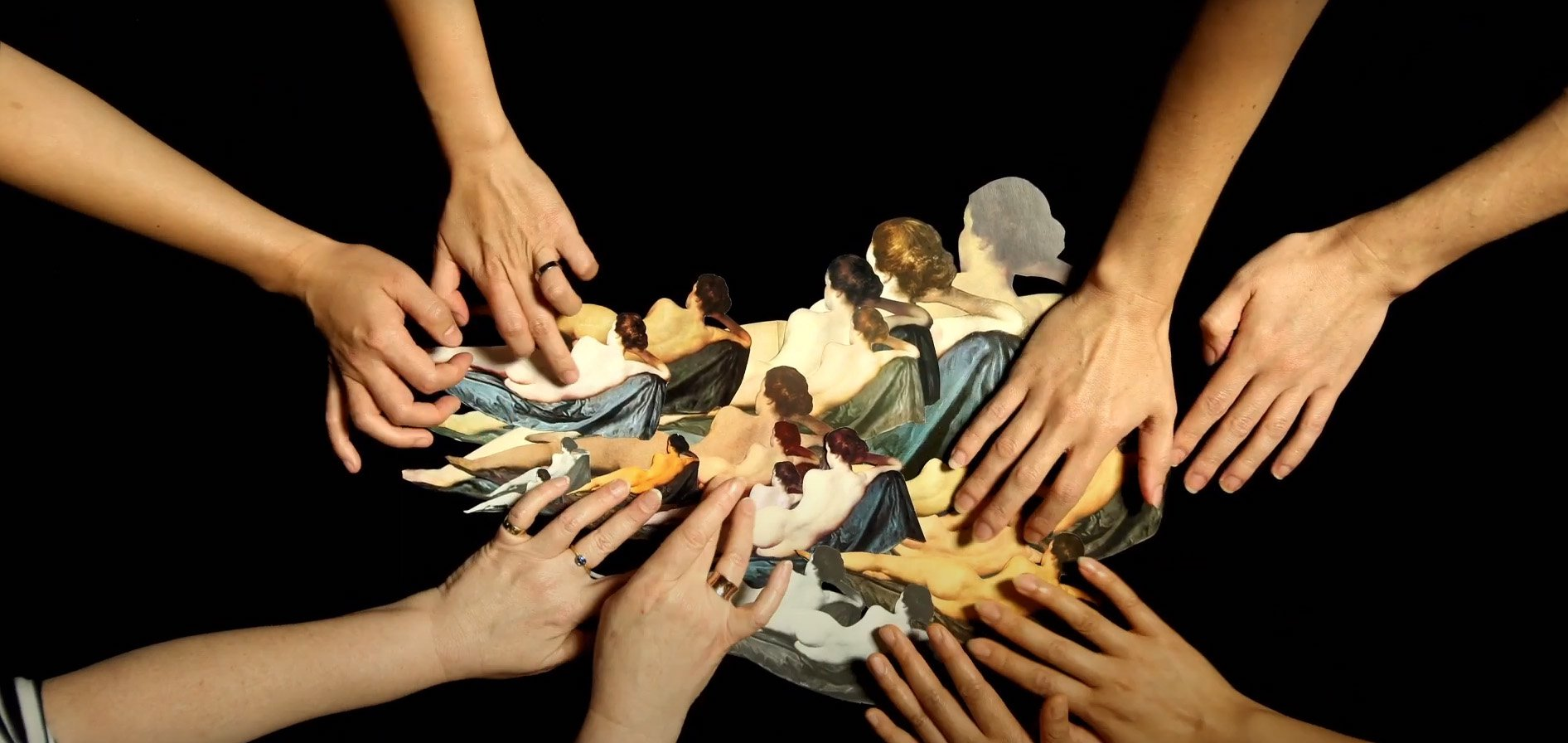 Many hands converging on a collage by Deborah Kelly as part of 'The Gods of Tiny Things'