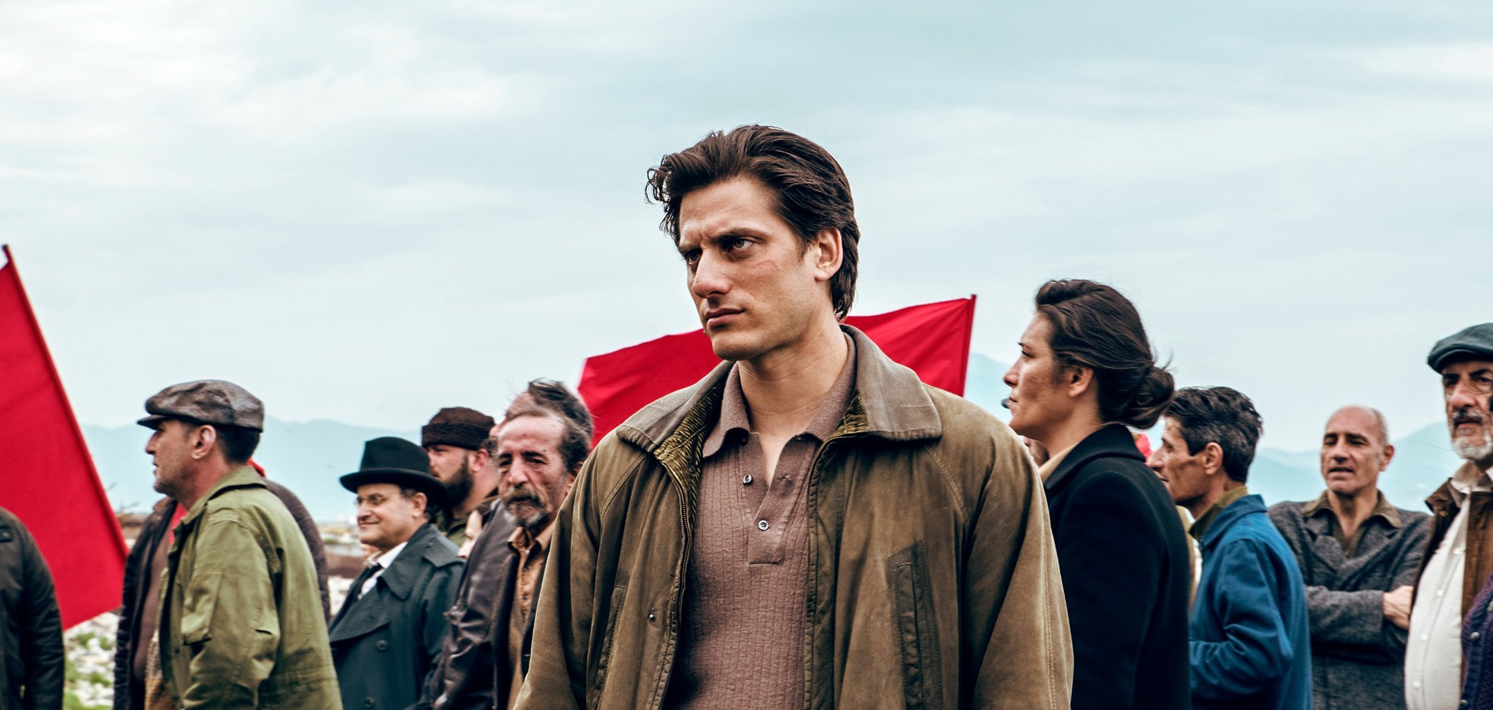 Luca Marinelli as titular character from Martin Eden, standing in front of a protesting crowd, some holding red flags