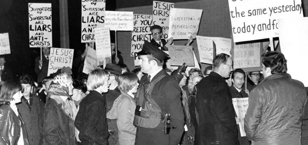 People protesting Jesus Christ Superstar while a policeman looks on