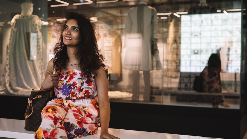 A woman in a floral dress and long dark hair sitting on a bench and looking at an installation in The Story of the Moving Image (image credit: Phoebe Powell)
