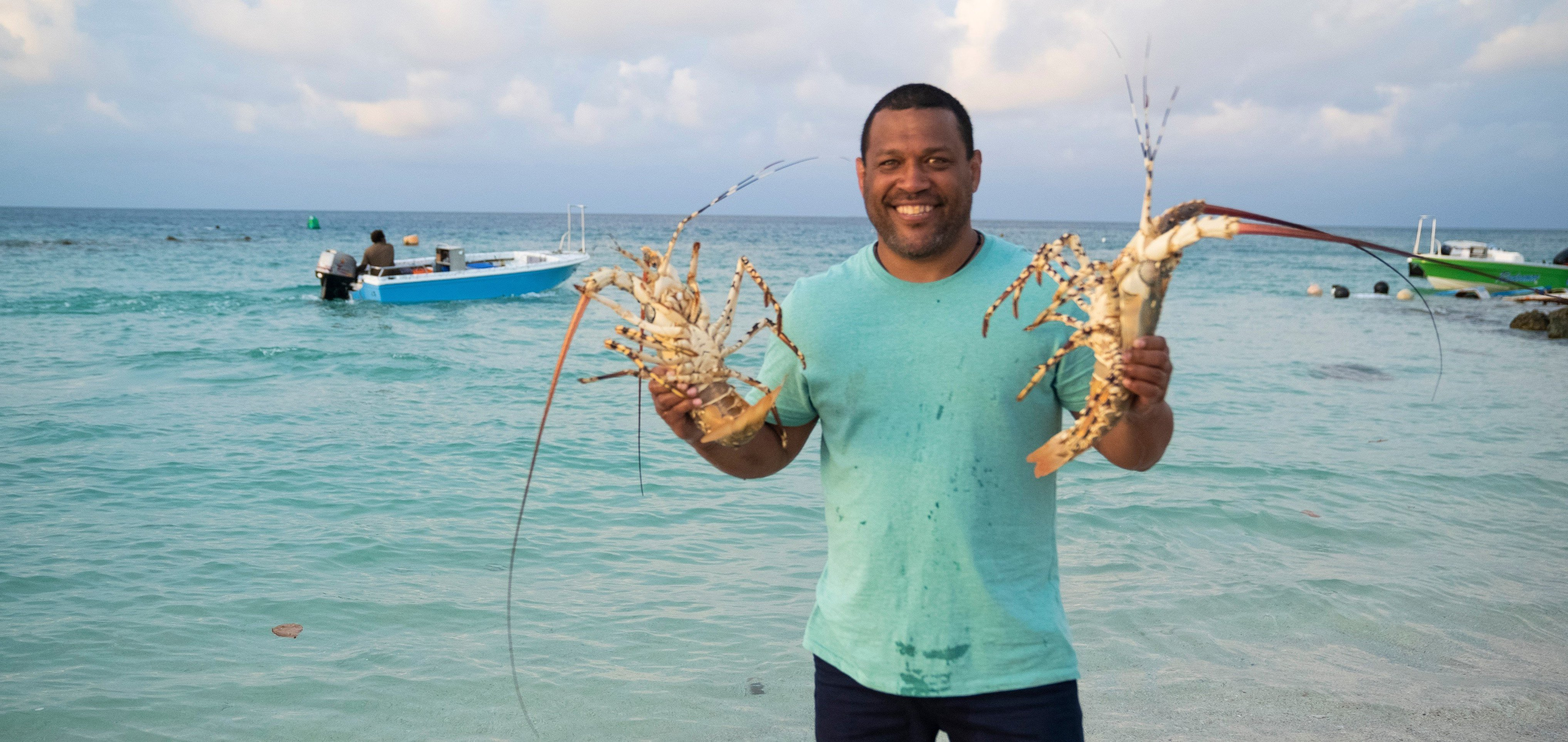 Promo shot of Aaron Fa'Aoso holding lobsters in each hand - NITV show Strait to the Plate (2021)