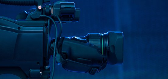 Side view of a black video camera on a blue background