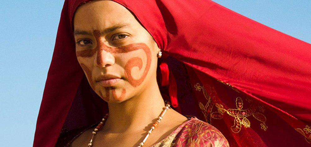 Closeup of a woman in a red headscarf and red and gold Colombian Indigenous dress. Still from Birds of Passage (2018)
