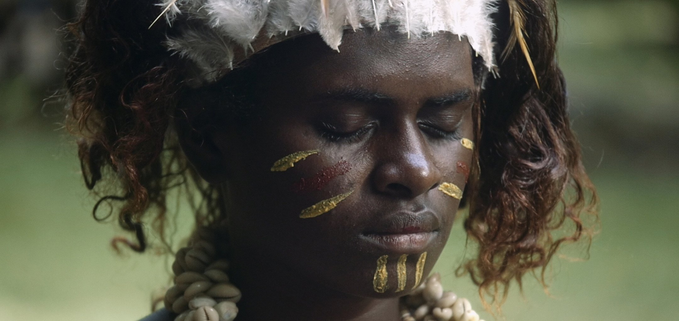 Still from Ophir - closeup of Bougainville woman with ritual face paint, eyes closed