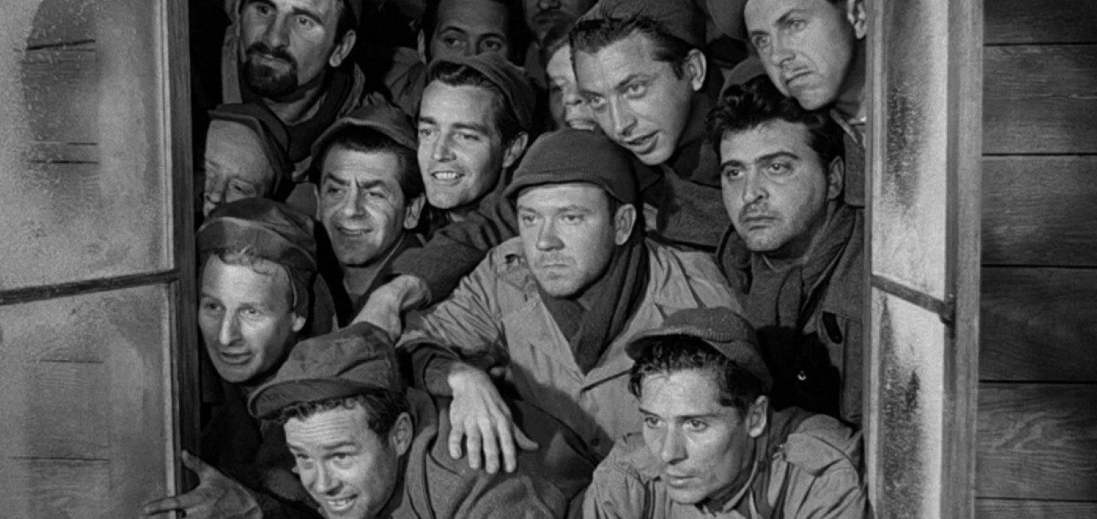 The inmate characters of Stalag 17 crowd together at a window
