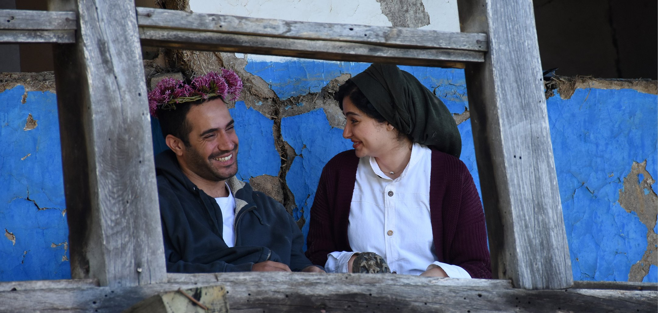 Mohammad Valizadegan and Baran Rasoulof smiling as Mohammad wears a flower crown in a still from 'There Is No Evil' (2020)