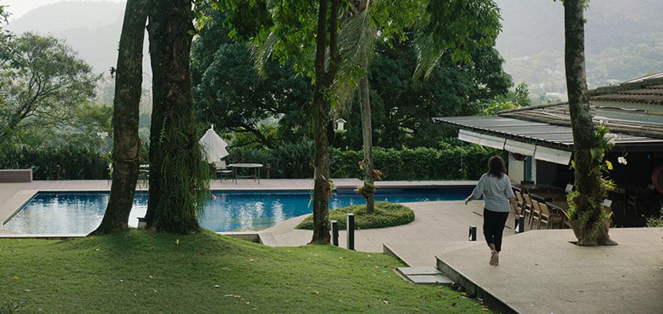 A woman strolling by a backyard pool in an idyllic setting in a still from 'Three Summers' (2019)