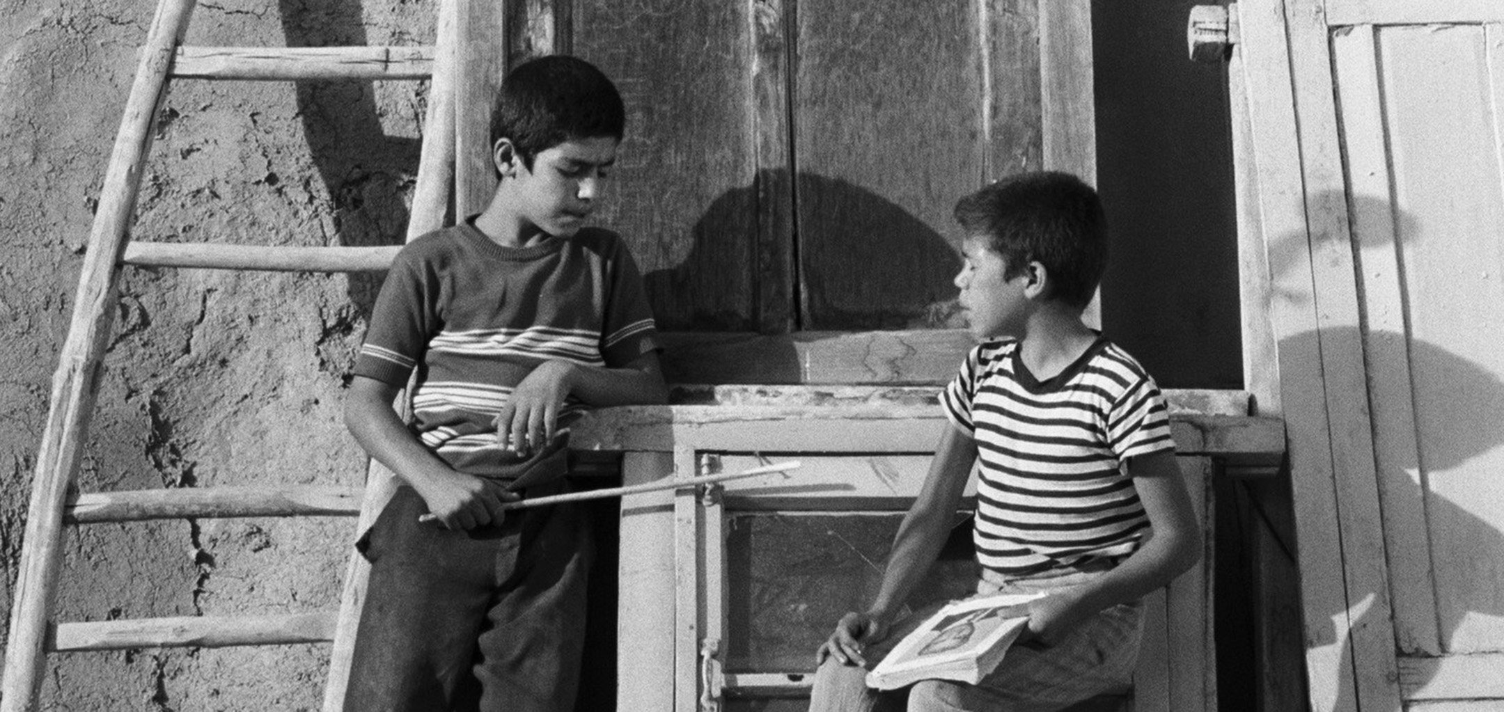 Two boys chattting outside a house in a still from 'Traveller'