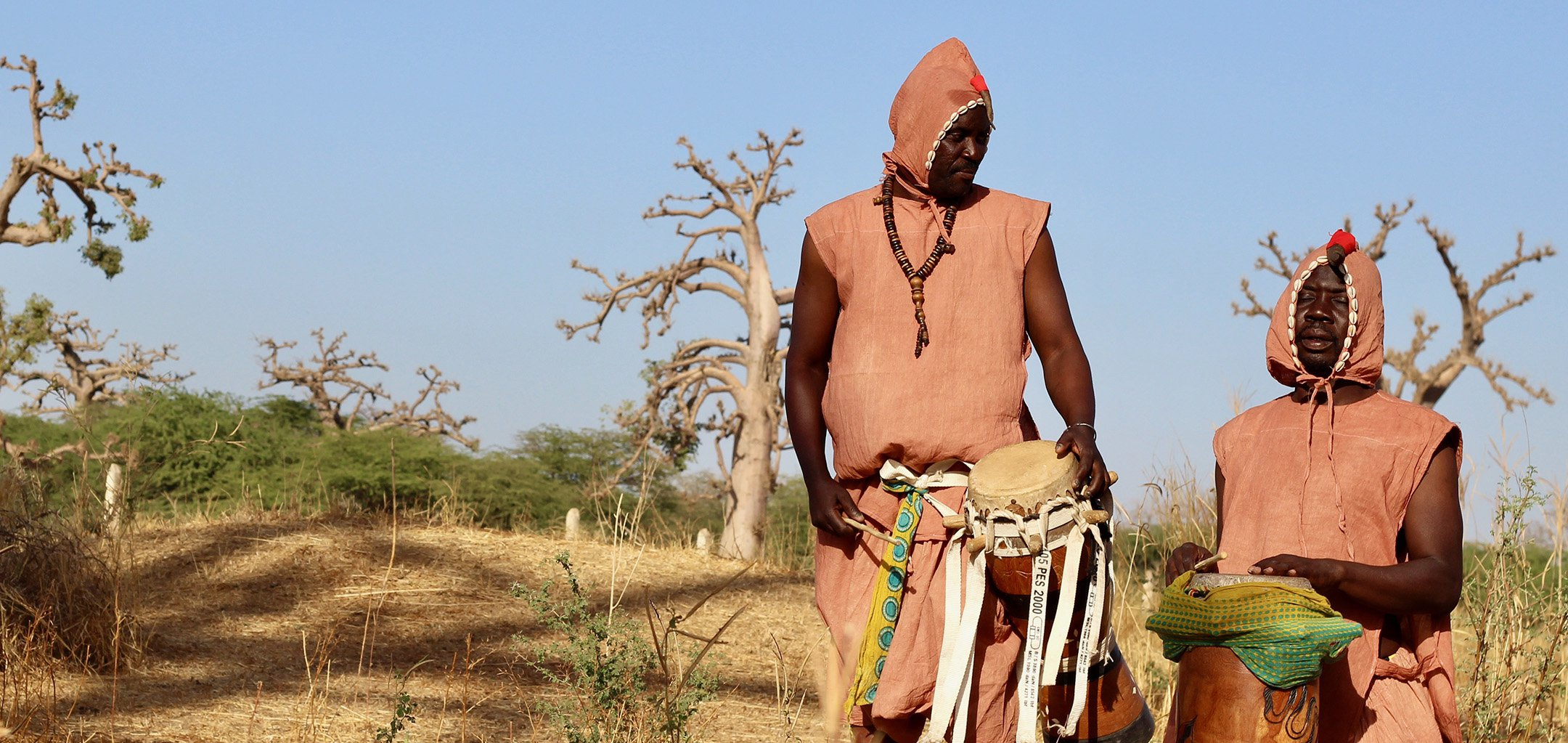 Two men in Senagalese tribal outfits playing music in a savannah - still from 'Deup' (2021) by Lamine Sonko