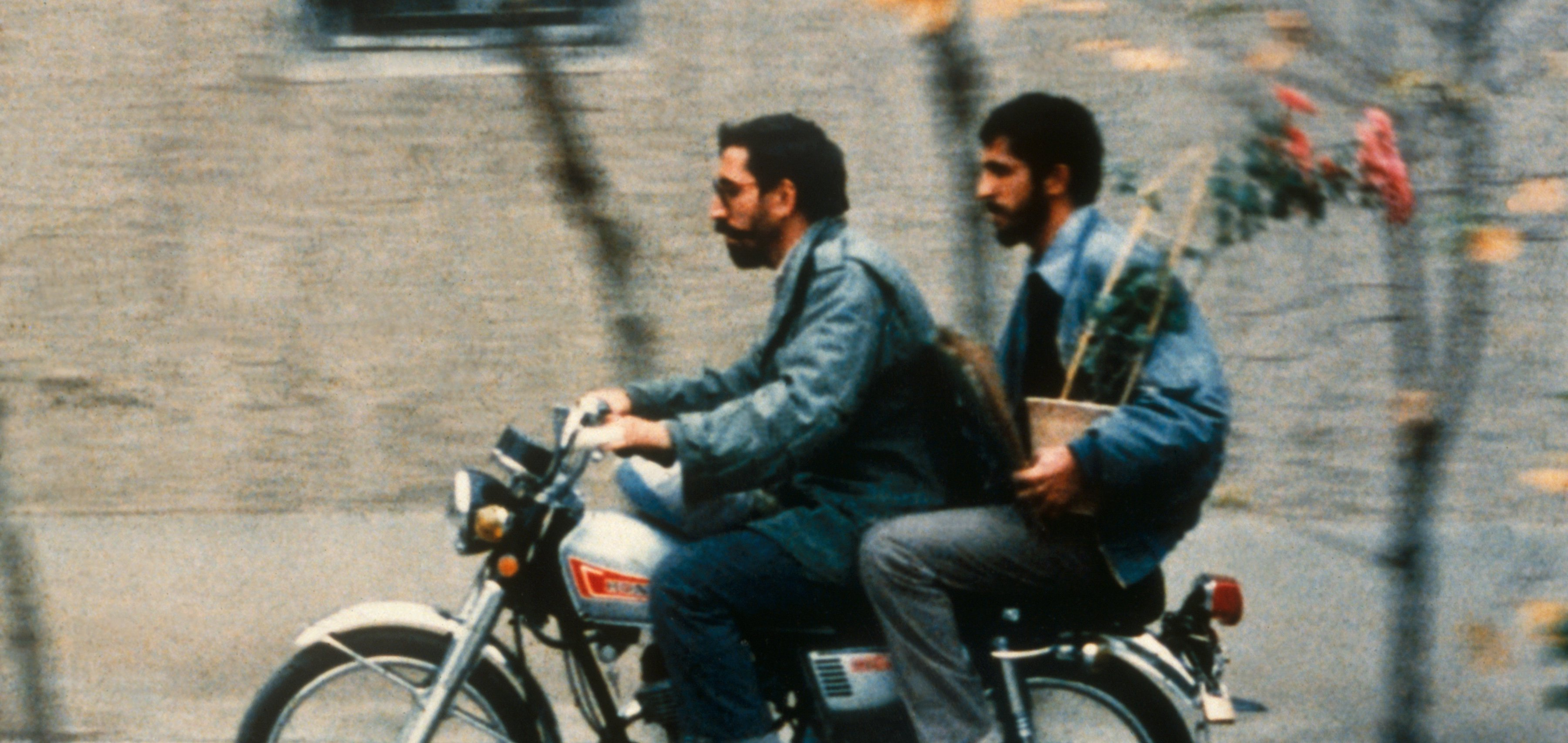 Two men on a motorbike, the one on the back holding a flowerpot in a still from Close-up (1990)