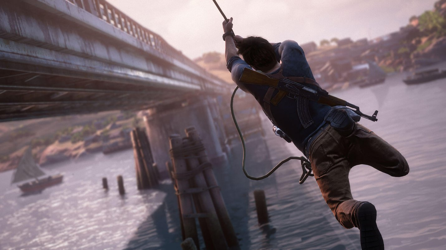 Uncharted 4 - A Thief's End (2016) - screenshot - Drake swinging from a rope to a bridge.jpeg