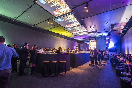 Underground Gallery at ACMI -  guests mingling in a bar style function space with screens on the ceiling