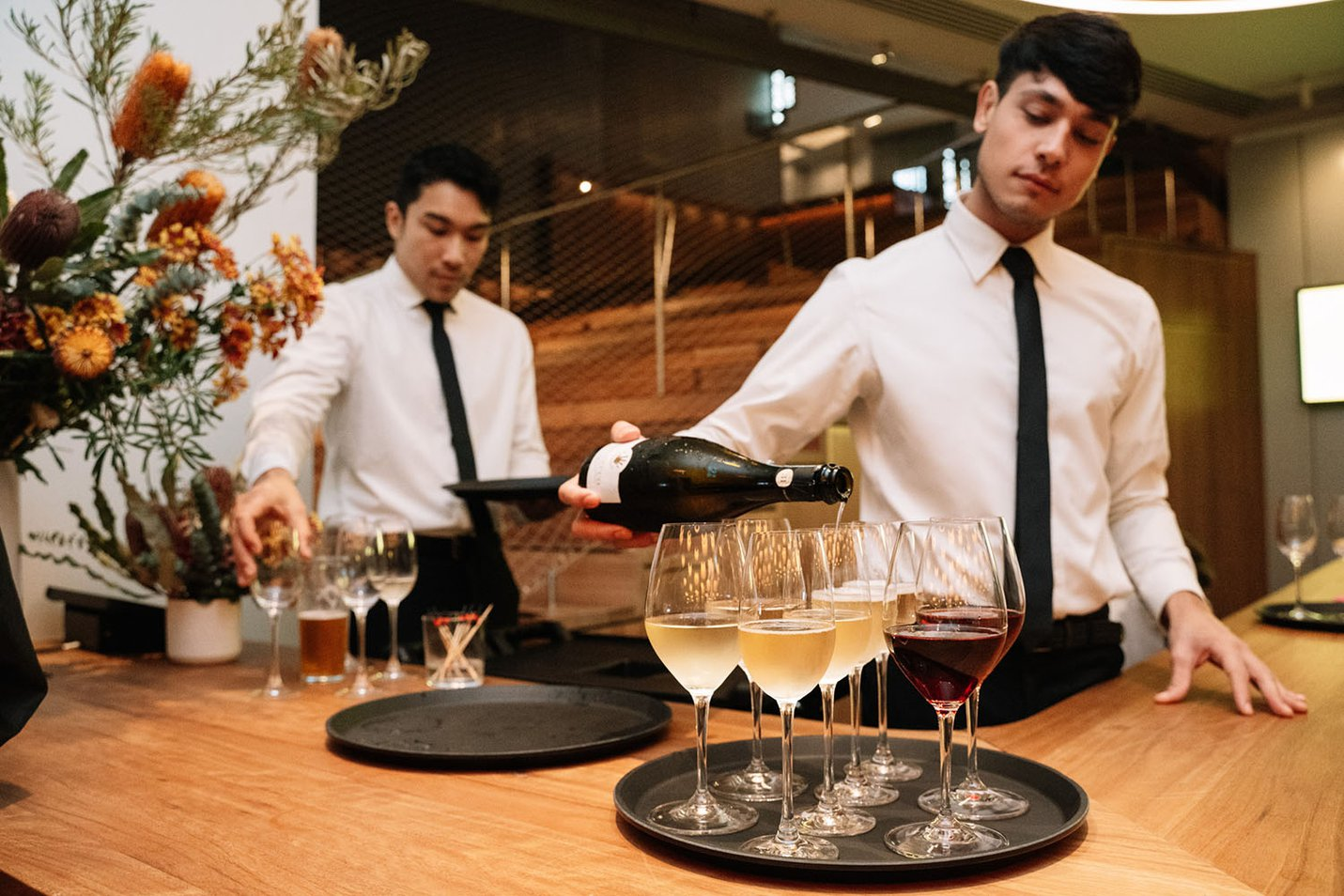 Wait staff pouring red and white wine at the opening of Disney - The Magic of Animation