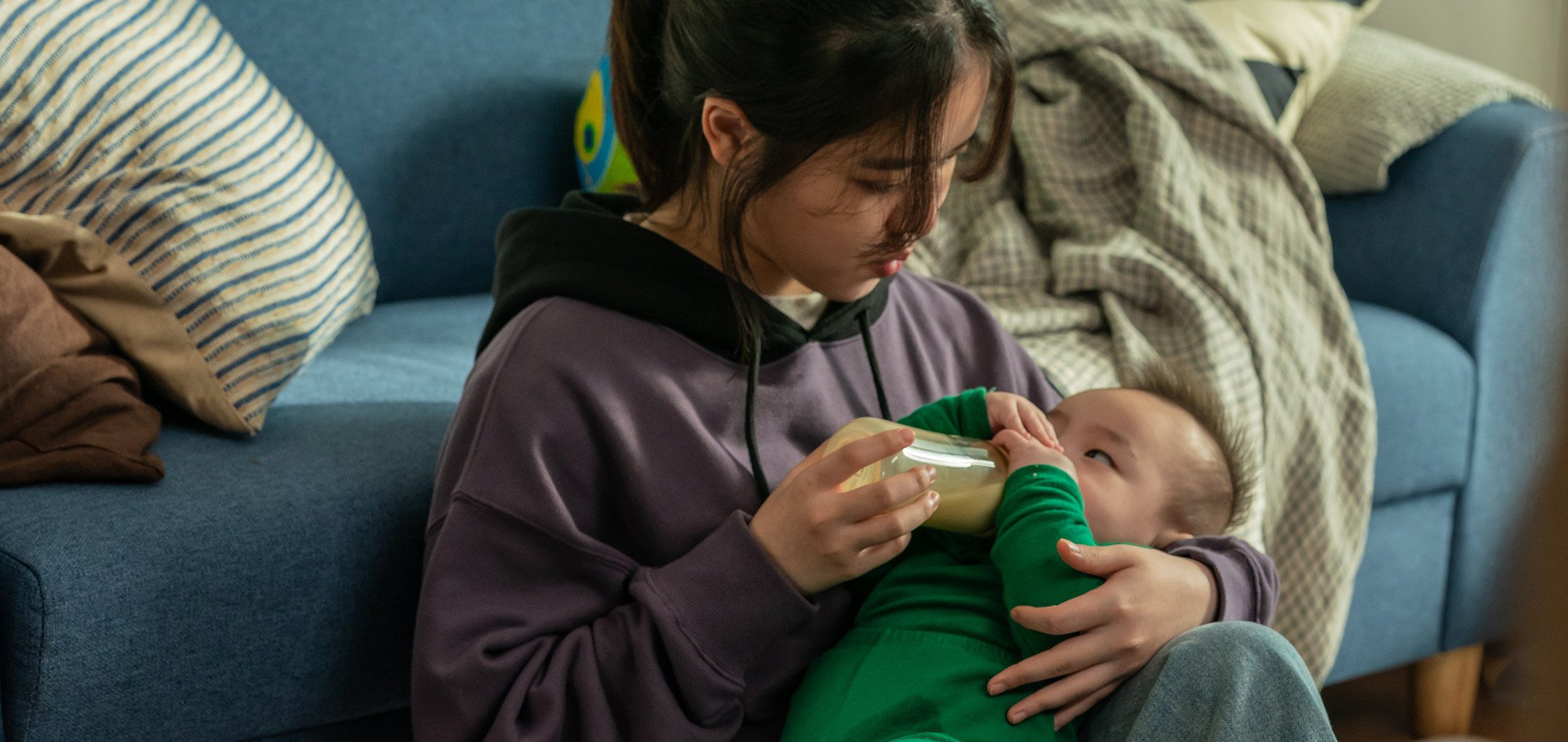 Young woman bottle feeding a baby in a stil from 'I' (2021)