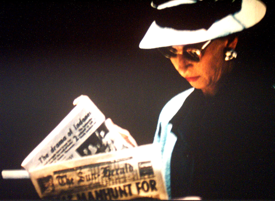 Woman reading a newspaper - a still from Sunday in Melbourne by Gil Brealey