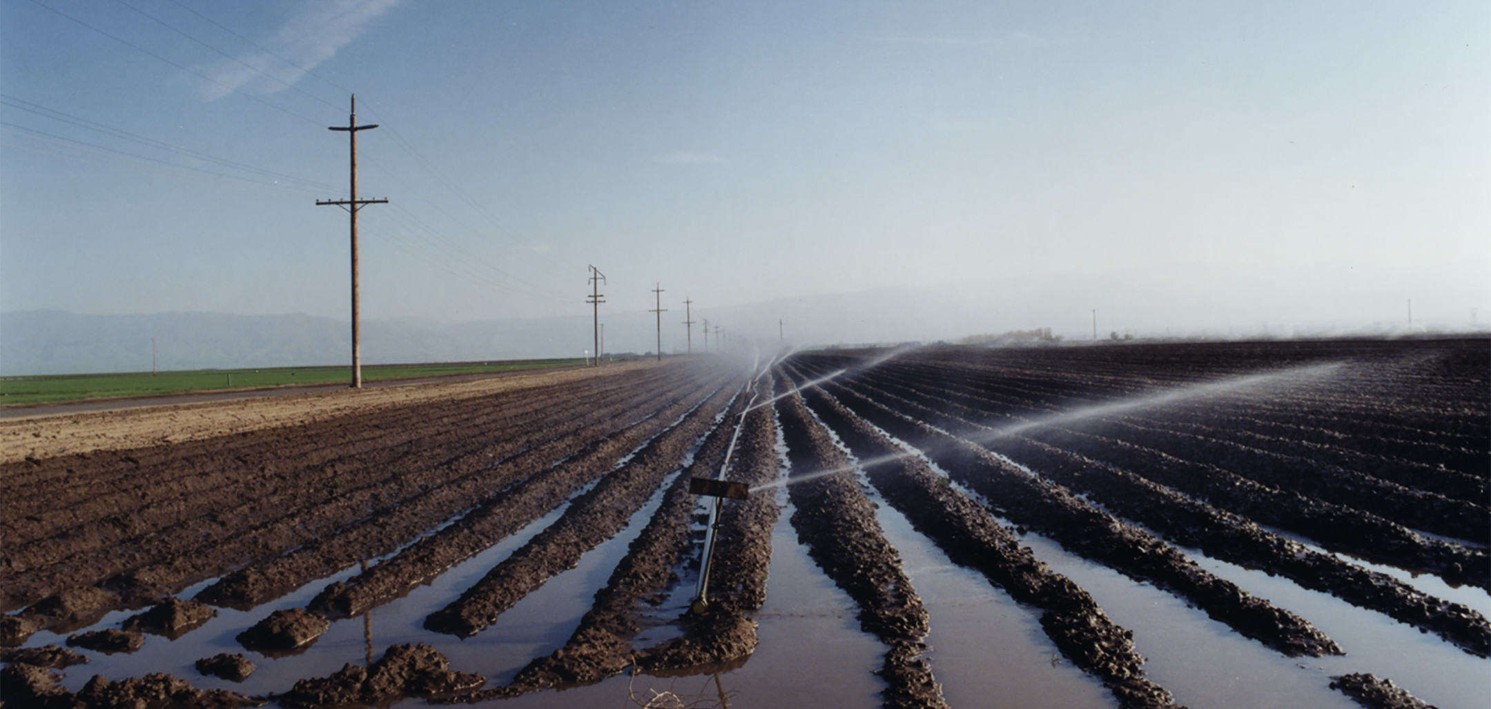 Irrigation channels and sprinklers on an empty farm field. Still from El Valley Centro (1999)
