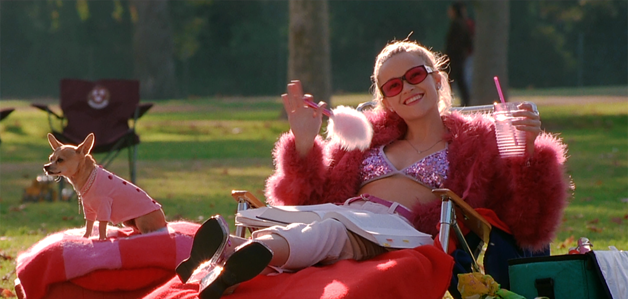 Reece Witherspoon as Elle, lounging on a red chair with her dog in a still from Legally Blonde (2001)