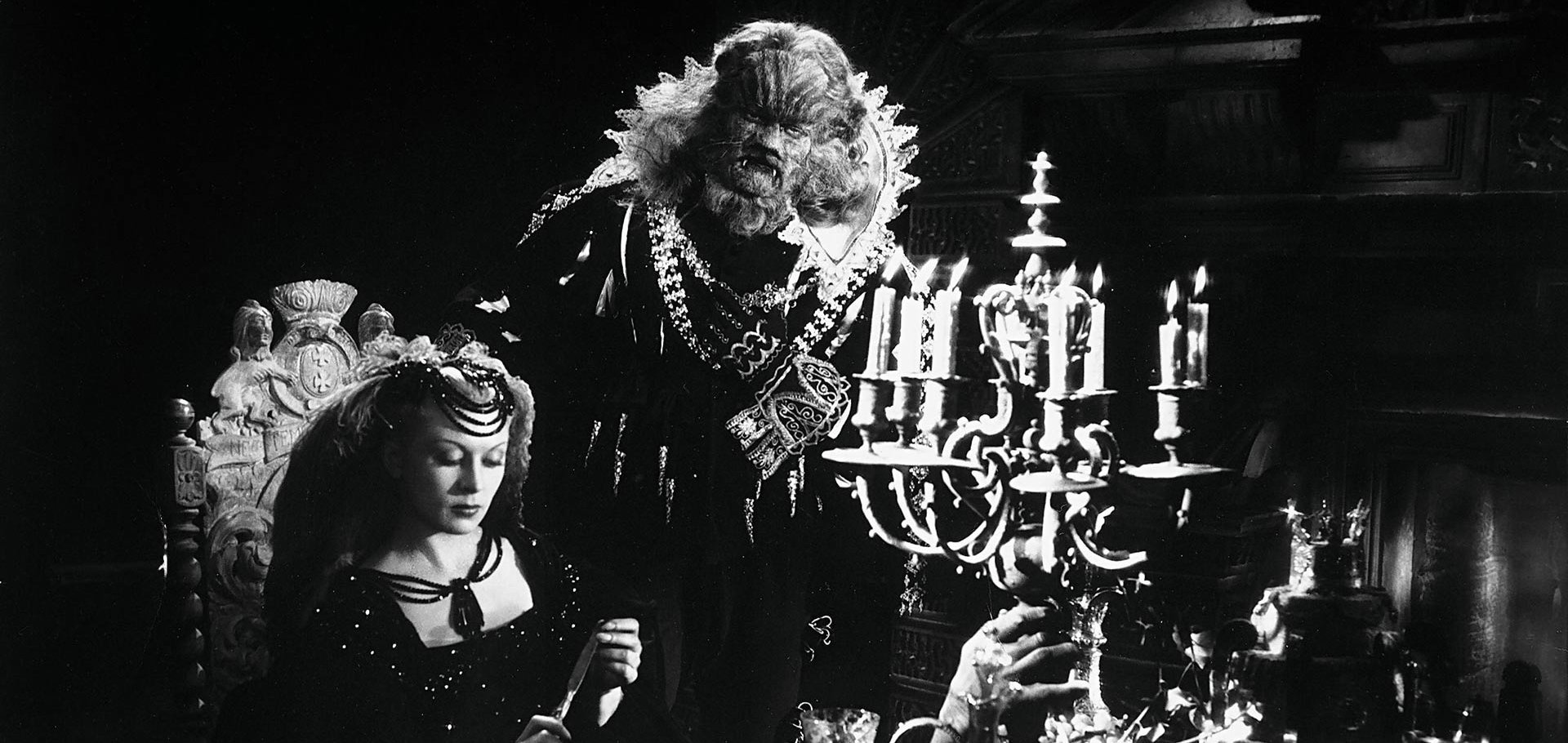 The Beast standing over Bell at the ornate dinner table in a still from 'La Belle Et La Bête' (1946)
