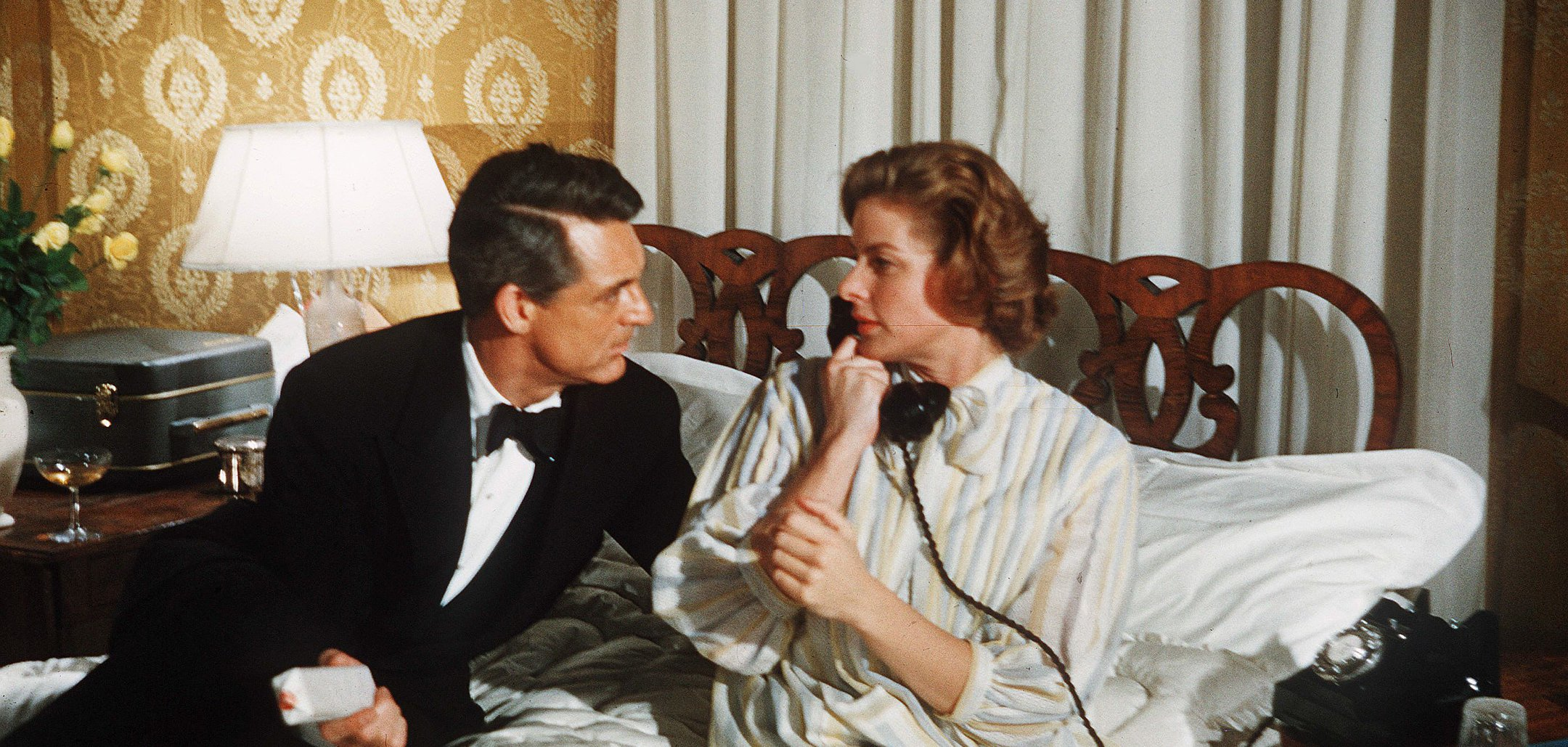 Cary Grant and Ingrid Bergman sit on a bed and look into each others' eyes in a still from 'Indiscreet' (1958)
