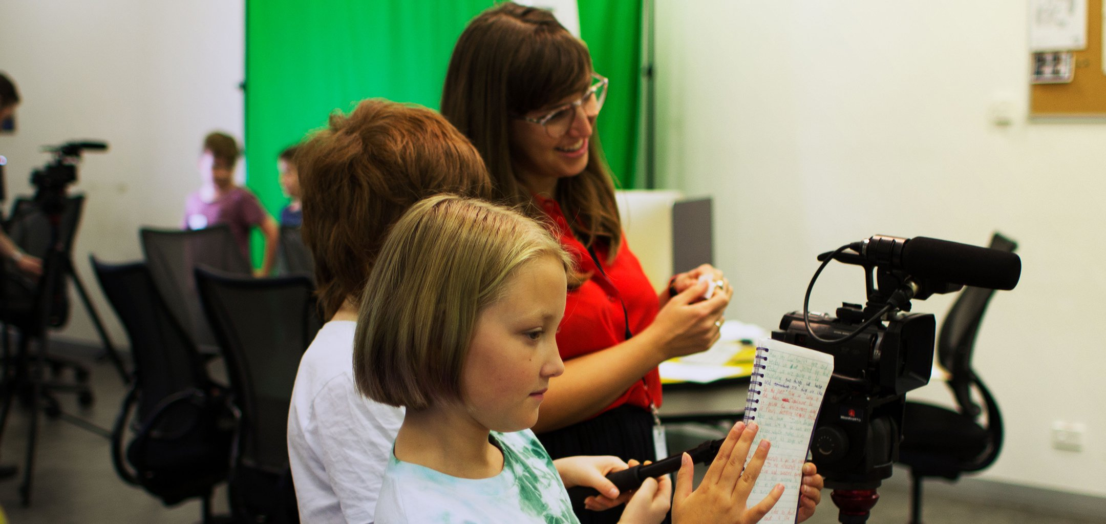 Kids holding a script and directing a film behind the camera with an instructor looking on, at ACMI