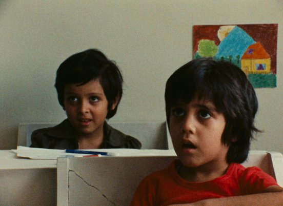 Two young boys attentively listening in a classrooom in a still from 'So Can I' (1975)