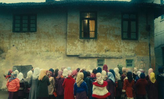 Kids in headscarves crowding around a building in a still from 'The Chorus' (1982)