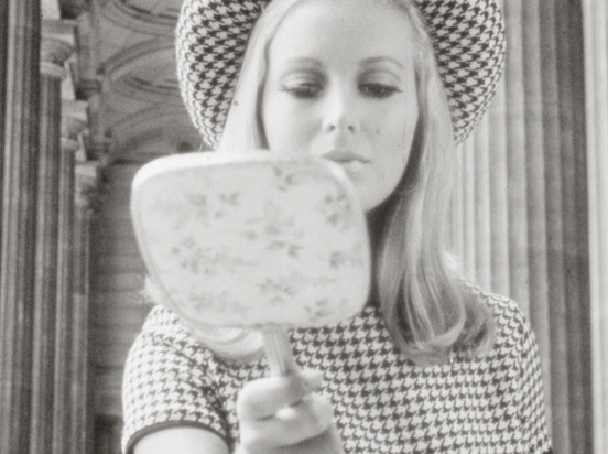 A model looks into a hand mirror - still from Wool Fashion Awards 1967
