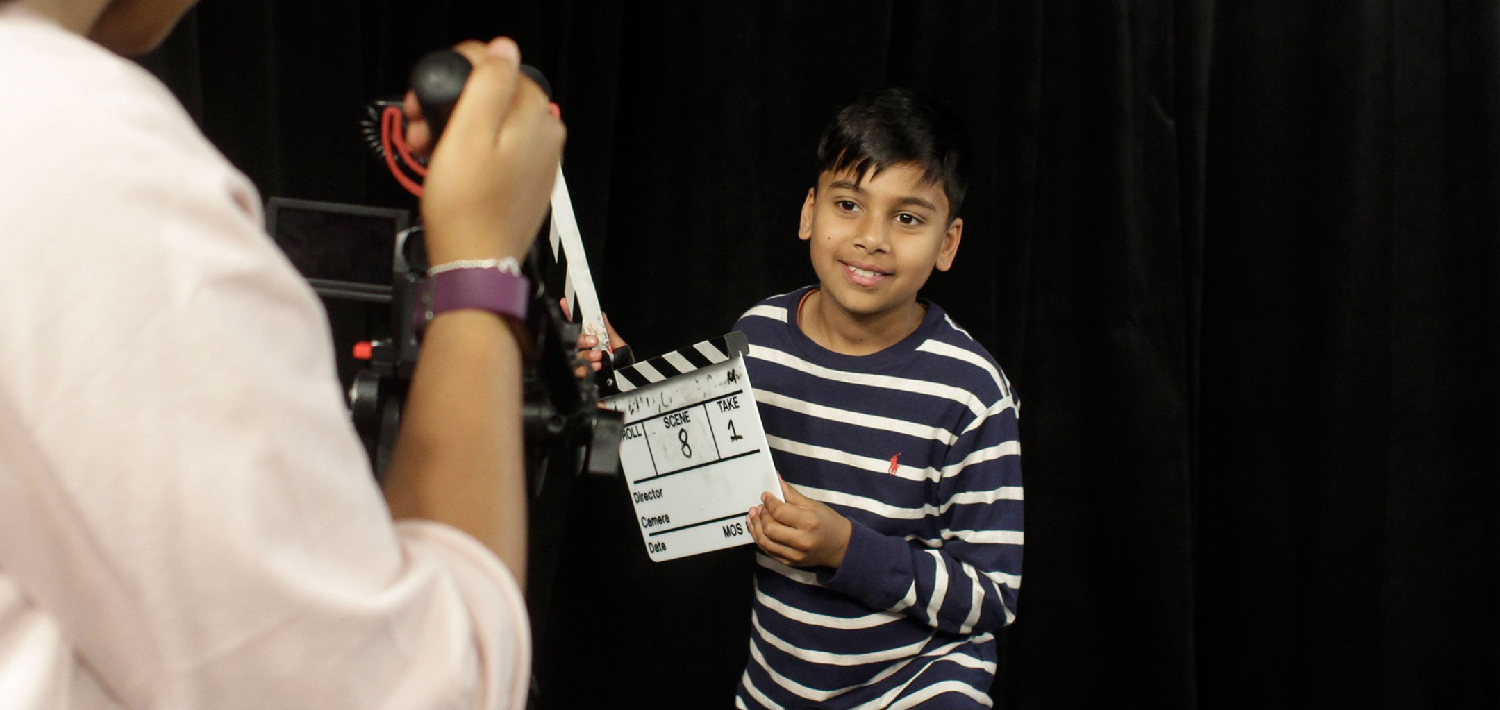 Kid holding a clapperboard in front of a black screen and a video camera